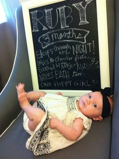 month-by-month picture with chalkboard that details what baby is doing at this age