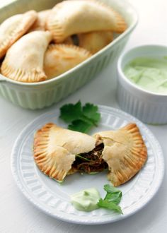 These empanadas are stuffed with shredded beef chiles lime spices onion and cilantro. An avocado cream sauce finishes the dish off. Avocado Cream, Avacado Dip, Mexican Dishes, Mexican Food Recipes, Latin Food, Beef Dishes, Pork Recipes, Yummy Recipes, Gourmet
