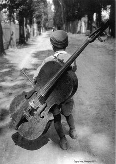 By Eva Besnyö    The gypsy boy with a cello on his back, an image of a homeless boy that's become world-famous. 1930