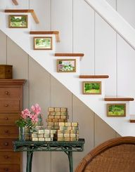 Home Art Gallery  The watercolors are by family friend Bonnie Egan, while the homes previous owner left behind the colorful vintage books.    Bright idea! Hang small artworks on staircase risers for unexpected visual appeal.