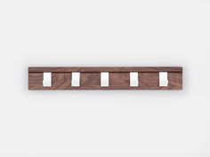 A solid walnut coat rail supplied with 5 cantilevered steel hooks. Each hook can be moved independently, locating into the 45 degree slots from which the product takes its name. Proudly made in the UK. Materials Available in Oak or Walnut, with white powder coated steel hooks. Dimensio