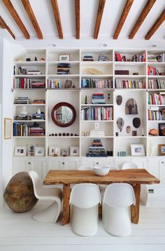 hanging a mirror and art breaks up a large, busy bookcase