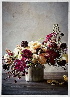stunning floral arrangement. i love the addition of the deep plum ranunculus.