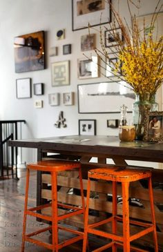 Kitchen Island with industrial Stools painted orange. Gallery Art wall in the background.