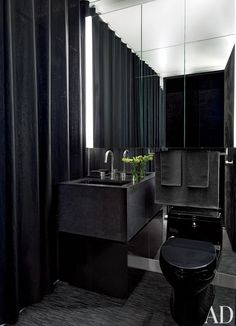 In an all-black bath, the vanity is granite, and the towels are by Calvin Klein Home.