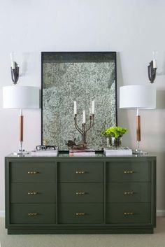 This custom made army green lacquered credenza with brass knuckle hardware is truly a one-of-a-kind. Vintage Art Deco wood and chrome lamps flank a vintage gold leaf mirror, adding richness and sophistication that complement the more modern lacquered credenza.