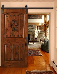 """6'8"""" 2 Panel BarnCraft rolling door with Florentine grille, square clavos, Philmont rolling hardware and Monterey pull handle. Shown with Knotty Alder in Traditional Canyon Brown stain option."""