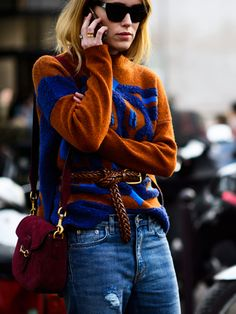A brown and blue sweater is worn with a brown leather belt cinched around the waist, jeans, a burgundy crossbody bag, and black sunglasses