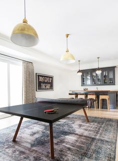 In the media room, a chic Ping-Pong table from 2Modern sits on top of a Shoppe by Amber Interiors rug. Thomas O'Brien brass pendants from Circa Lighting ensure there's plenty of light for late-night games. In the back, Jayson Home stools are pulled up to the bar.