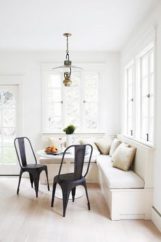 Crisp white and cream dining space with bench seating and matte black chairs, a small round table, lantern lighting, and large windows.