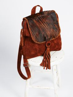Caiman Backpack | All leather suede backpack with a top foldover featuring cool calf hair and a western-inspired tassel detail. Back handle and adjustable straps for an easy carry. Zipper closure. Lined inner with pockets for storing.