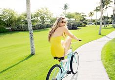 Girl in all yellow ensemble riding a blue bicycle.