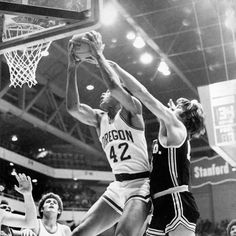 Black and white photo of University of Oregon basketball player Greg Ballard securing a rebound during a game played on December 19, 1973 at McArthur Court. Also pictured are Ducks Bruce Coldren (lower left) and Ronnie Lee (lower right). ©University of Oregon Libraries - Special Collections and University Archives