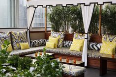 Gorgeous city deck with white fabric canopy with black trim, white drapes, Trina Turk Peacock Print in Driftwood pillows & cushions, yellow geometric pattern pillows and black & white bolster pillows.
