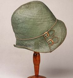 A pale green straw cloche with contrast trim and metal buckle details on the brim... late 1920s-1930s.