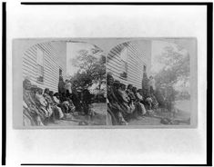 1868 photo of Group of Winnebago Indians seated on bench outside of building