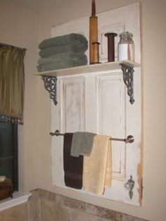 Maybe an old narrow closet door, stained grey-brown to mount on the bathroom wall, then put shelves/towel bars on it