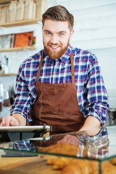Potrait of happy bearded barista at work in coffe shop by vadymvdrobot. Potrait of attractive happy bearded barista in brown apron at work in coffe shop Customer Day, Black Press, Male Man, Modern Graphic Design, Barista, Coffee Shop, Stock Photos, Happy, Apron