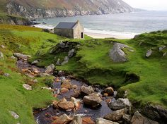 A stone cottage stands sentinel on the coast of Achill Island in County Mayo, Ireland. Mayo's rugged coastline is part of the Wild Atlantic Way scenic route, which covers 1,491 miles of Ireland's untamed western coast.