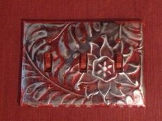 Metal embossed light switch cover using Ten Seconds tools & metal. Added some Tim Holtz alcohol inks to distress a bit.