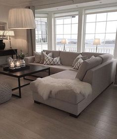Neutral Living Room Inspiration | Grey Sectional | Hardwood Floors | Large Windows | Modern Black Coffee Table