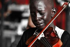 The boy who cries in the photo is Diego Frazao Torquato, who played the violin in the String Orchestra of the Afro Reggae. Afro Reggae is a non-profit organization that gives kids hope and an escape from negative environments. The occasion was the funeral of his social project coordinator, Evandro João Silva, who was murdered in downtown Rio. Diego contracted meningitis at age four, aggravated by pneumonia, and struggled with memory difficulties. He still managed to learn th