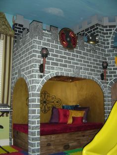 """Castle Playroom, Bedroom to playroom conversion.  Two story castle has toy storage in the """"dungeon"""" and underneath the oversized cushioned lounging area. Floor to ceiling tower is actually a climbing wall.  Castle surface"""