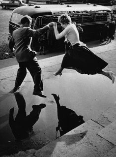 A man gives a woman a helping hand as she takes a flying leap over a large puddle on the pavement, 1960