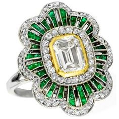 This is fabulous diamond emerald gold platinum engagement ring from the Art Deco period. Is centered with a stunning emerald cut diamond that weighs 0.76ct. The color of this diamond is F with VVS clarity. The center stone is set on contrasting 18k yellow gold bezel; and is accentuated small rose and old mine cut diamonds that weigh approximately 0.75ct. The diamonds are accentuated by bright French cut calibre emerald accents.The ring has a wonderful open work and milgrain design.