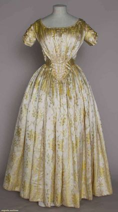 YELLOW SILK BROCADE BALLGOWN, 1840s. Ivory satin brocaded flowers & trailing ribbons & bows in vertical stripe pattern, long V-front fan-pleated waist, piped, short sleeves, leno weave buckram skirt lining & glazed cotton hem facing.