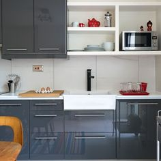 Grey cupboard fronts have been teamed with open shelving and large white Italian porcelain tiles to help soften the look and keep the room feeling bright and airy.  Units   Ikea  Paint   Farrow & Ball