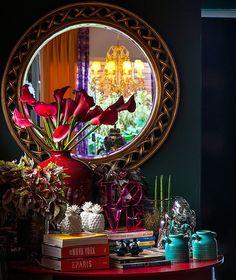 Cantinho do living com espelho, lembranças de viagens, livros e flores (Foto: Divulgação/Romulo Fialdini)