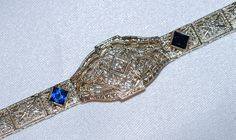 Art Deco lady's 14 karat white gold .10pts Diamond and Sapphire bracelet. The filigree box link style bracelet has an oval center plaque that is bead set with one Old Mine cut diamond. C.1930's.