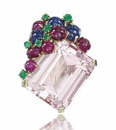 Composed of a cluster of carved ruby and emerald leaves with cabochon ruby and sapphire berries and single and brilliant-cut diamond accents, to the cabochon sapphire and vari-cut diamond vase, 1929, French marks for platinum, 4.4cm long, with associated maker's case  Signed Cartier Paris and no.03308