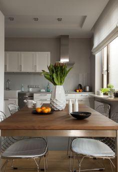 Biała kuchnia urządzona jest bardzo funkcjonalnie. Styl angielski nadaje kuchni charakteru, jednak połączenie prostych form z połyskującymi elementami i szarym kolorem ścian, doskonale pasuje do nowoczesnego wnętrza. Biała kuchnia ZDJĘCIA.