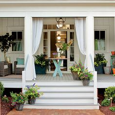 Farmhouse Porch | Visible from the front door, the back porch's centered round table offers a pretty place for flowers or serving during a party. | SouthernLiving.com
