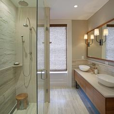 A mix of neutral tones and clean, crisp lines turn this master bathroom into a tailored, peaceful oasis. The floors and shower walls add welcome texture to break up the many smooth surfaces.