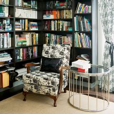 black bookshelves & chair, black & white toile armchair, modern glass side table,