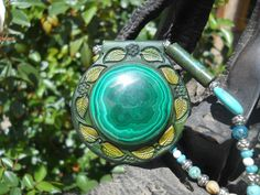 Leather pendant set with 40mm round malachite cabochon. Strung with turquoise, moss agate,howlite and silver-plated brass beads. Silver-plated brass fob clasp. $160. BP6.