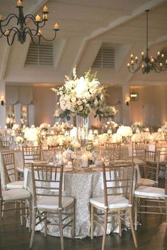 Gold ivory and white wedding reception decor with white florals in glass vessels place settings of gold-rimmed crystal and gold-rimmed glass chargers floating candles textured linens and natural wooden chairs. Event design and florals by Bella Flora Wedding Table Linens, Wedding Reception Centerpieces, Wedding Table Settings, Table Centerpieces, Place Settings, Reception Ideas, Reception Party, Centerpiece Ideas, Wedding Receptions