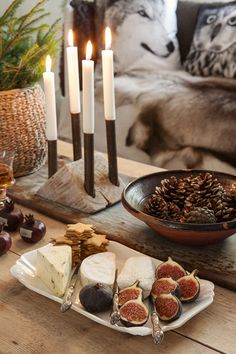 Gorgeous and neutral Swedish Christmas decor inspiration from Anna Truelsen who has styled figs and cheese on a tray, multiple candles, and a bowl of pinecones for a cozy holiday moment.