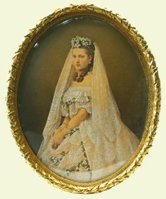 Princess Alexandra in her wedding dress. Princess Alexandra of Denmark was married to Albert Edward, Prince of Wales, on 10 March 1863. She was given a suite of Brussels lace to wear but Queen Victoria declared it inappropriate. She decreed that the dress of the future Queen of Britain must be entirely of British manufacture, trimmed with English lace. This painted photograph shows Alexandra wearing the English lace overlaid with swags of artificial orange blossom.
