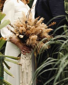 A Wedding Trend We're Loving: Macramé Decorations | Martha Stewart Weddings - This bride added a whimsical touch to her dried eucalyptus and pampas grass arrangement (by The Pear Blossom) with a dramatic Ballantyne Design macramé bouquet wrap.