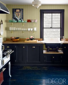 The custom-made cabinetry is painted in Tanner's Brown, and the walls are in Cream, both by Farrow & Ball; the countertops are butcher block, the sink fittings are by Waterworks, and the Wedgewood stove is antique.   - ELLEDecor.com