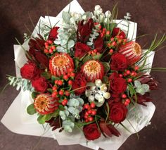 "A beautiful mix of Australian native flowers and wildflowers in this bouquet : orange hypericum ""Coco Rio"" ; coral-red Banksia coccinea, silvery-white Eucalyptus tetragona nuts, wine-red Leucadendron 'Safari Sunset', green barker bush foliage & Eucalyptus silver dollar from Western Australia; and rose ""Rhythm""."