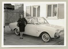 https://flic.kr/p/qpm3sM   Ford Taunus 17M   A cheerful young lady dressed in the fashion of the early sixties posing with a seemingly brand new Ford in front of the family home. The car is registered in the West German district of Büdingen.  Country of origin: Germany