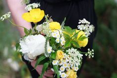 Spring wedding bouquet by Bleedfoot Florals. Small cute bridesmaids bouquet with white and yellow peonies Icelandic poppies, oregano, queen annes lace, raspberry, chamomile, beautiful ranunculus. Fresh happy yellow brides color scheme, yellow silk ribbons, loose and garden style.