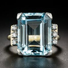 Mid-Century Aquamarine and Diamond Ring. Sturdily and artfully crafted in two-tone gold, circa 1940s-50s, this classic Retro cocktail ring glistens loud and crystal clear with a placid pastel blue, emerald-cut aquamarine, weighing approximately 13 carats. The soothing gemstone is embraced east and west with trios a small diamond sparklers, and north and south with a fluted side gallery in white gold.