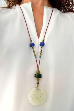 Colgante oriental de jade color blanco con cuentas de cristal verde, cuentas de cristal reciclado africano, cuentas metálicas y cuero redondo color frambuesa. Cierre de zamak bañado en plata.