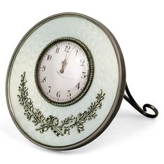 A FABERGÉ SILVER AND GUILLOCHÉ ENAMEL DESK CLOCK, WORKMASTER HENRIK WIGSTRÖM, ST PETERSBURG, 1899–1903. Circular, with seed pearl bezel and beaded border, the surface enamelled in translucent oyster white over moiré engine-turning and applied with ribbon-tied sprays of laurel.